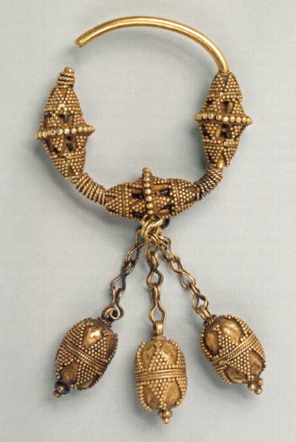 Золотое кованое височное трёхбусинное кольцо с подвесками, украшенное зернью. Кольца гнулись из круглого дрота, на который насаживались желудевидные бусины. XI — начало XII в. ГИМ.